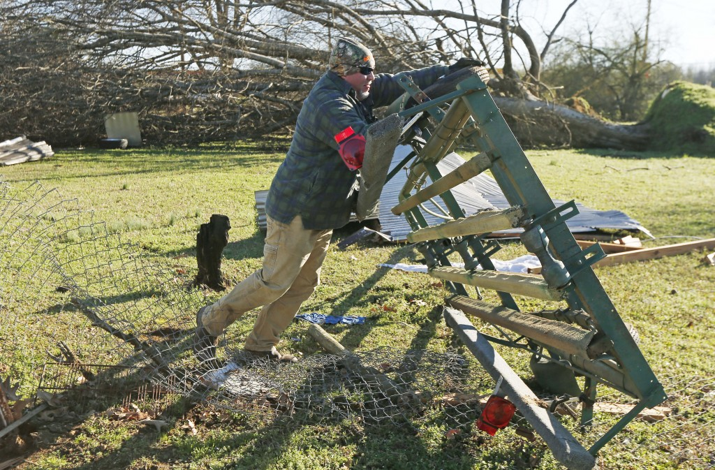 Jack Gordman flips over a boat trailer that was tossed several feef from his parent's home in Columbus, Miss., Sunday morning, Feb. 24, 2019, after Sa