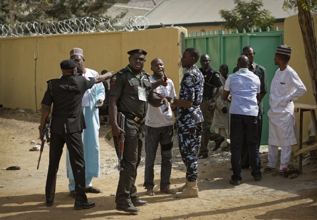 Police attempt to calm opposition supporters who entered a vote compilation center to allege irregularities, before being ejected, in Kano, in norther