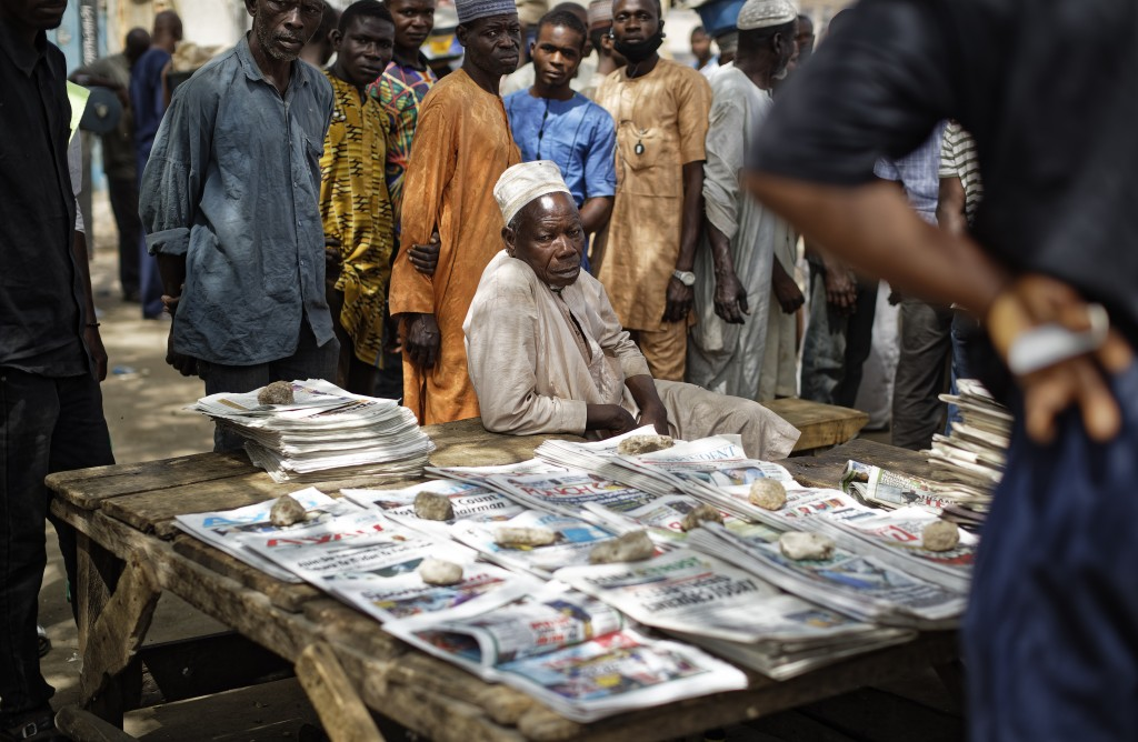 Nigerians gather around to look at the day's front pages at a newspaper stand in Kano, in northern Nigeria Sunday, Feb. 24, 2019. Vote counting contin...