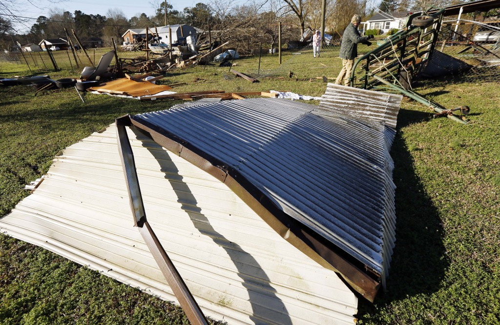 Tornado strewn debris, including this roofing, and fallen trees in this Columbus, Miss., neighborhood, Sunday morning, Feb. 24, 2019 after Saturday's