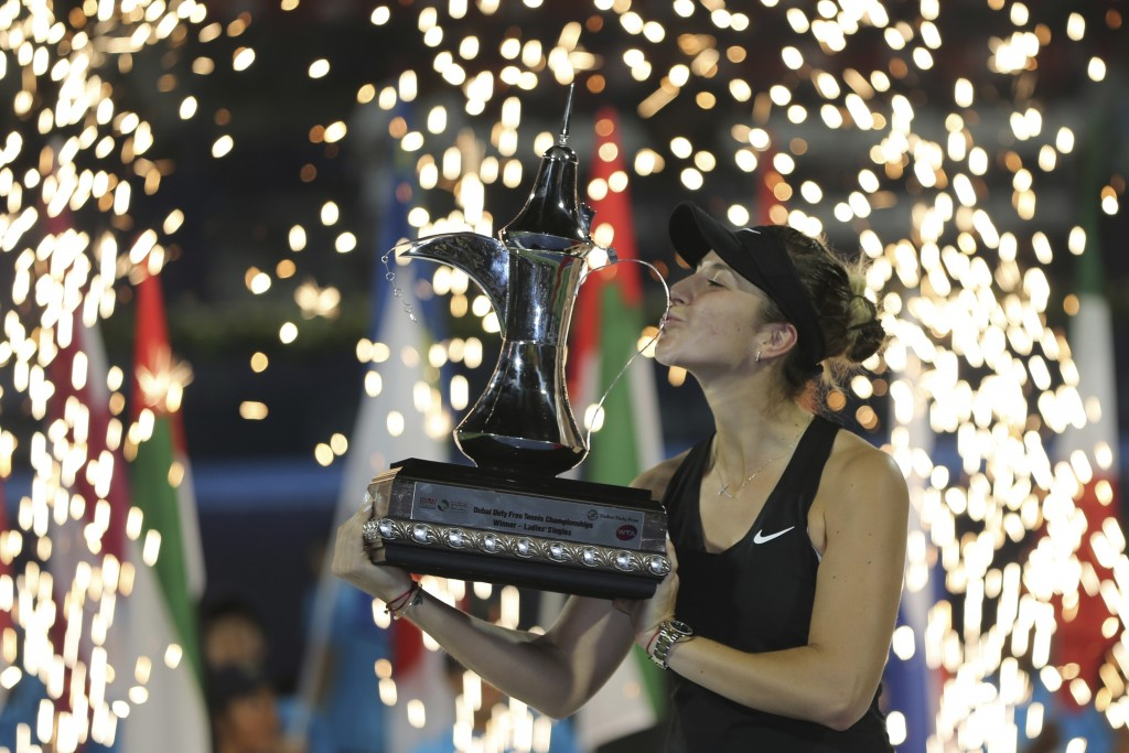 Switzerland's Belinda Bencic kisses her trophy after defeating Czech Republic's Petra Kvitova during their final match of the Dubai Duty Free Tennis C...