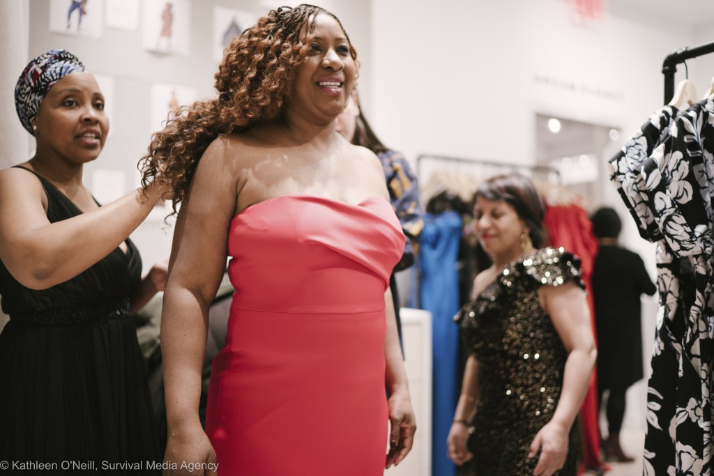 In this photo provided by Survival Media, women who work in the domestic industry try on dresses for Oscars viewing party at Rent The Runway on Wednes