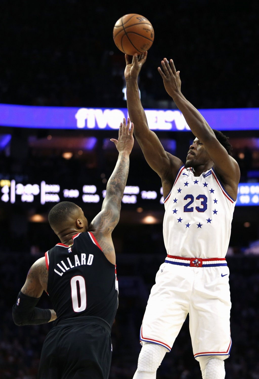 Philadelphia 76ers guard Jimmy Butler (23) takes a shot over Portland Trail Blazers guard Damian Lillard (0) during the first half on an NBA basketbal