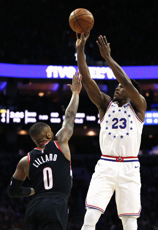 Philadelphia 76ers guard Jimmy Butler (23) takes a shot over Portland Trail Blazers guard Damian Lillard (0) during the first half on an NBA basketbal...