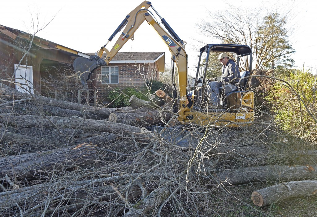 A backhoe is used to removes fallen tree limbs in this Columbus, Miss., neighborhood, Sunday morning, Feb. 24, 2019. At least one person was killed am