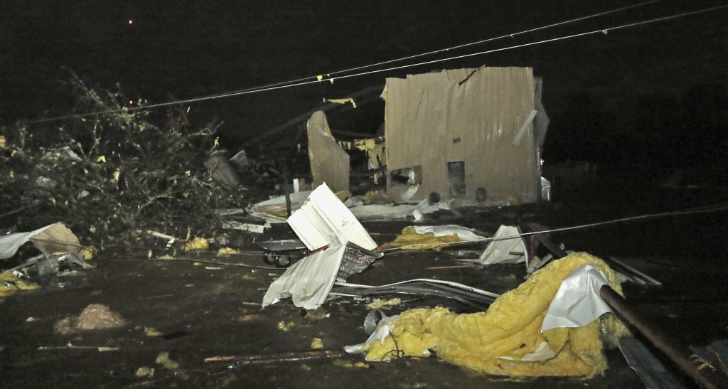 Downed power lines, trees and building debris from businesses including B.J.'s Dog Grooming liter Conway Drive in Columbus, Miss., after a tornado str...