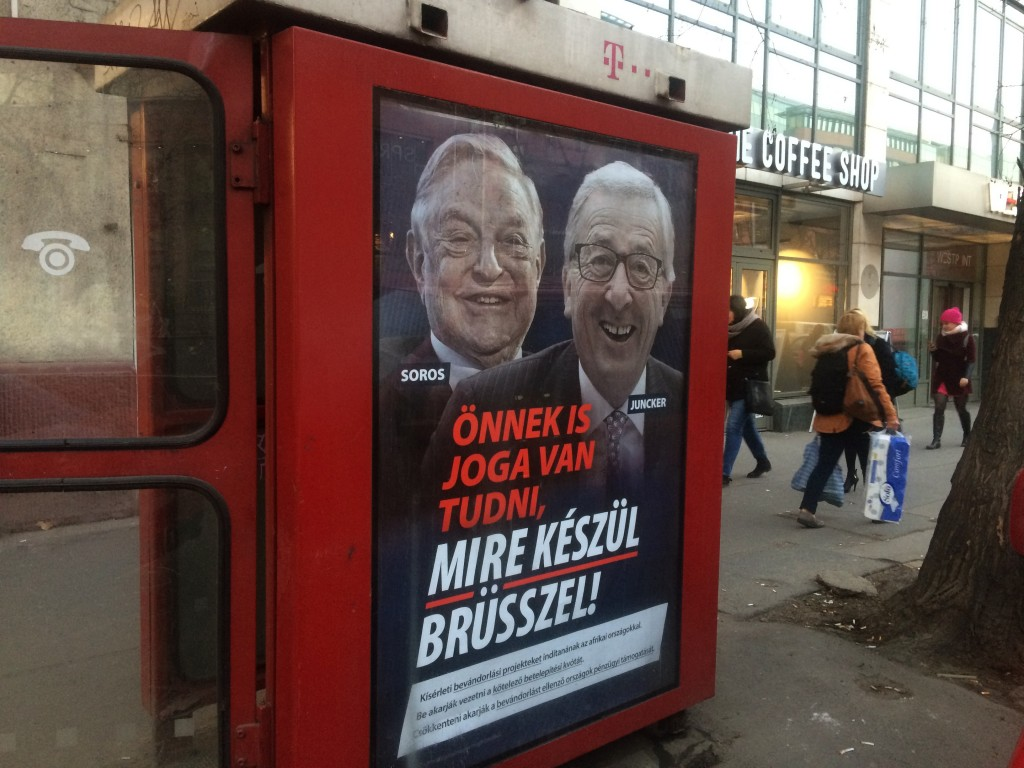 FILE - In this Feb. 19, 2019 file photo, a phone box displays a billboard showing Hungarian-American financier George Soros and EU Commission Presiden