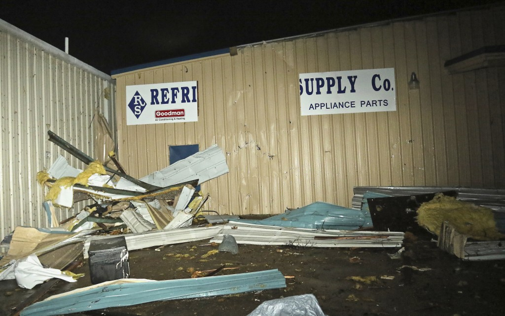 Tin from nearby businesses is piled up in front of Refrigeration Supply on Conway Drive in Columbus, Miss. after a tornado struck the area Saturday, F...