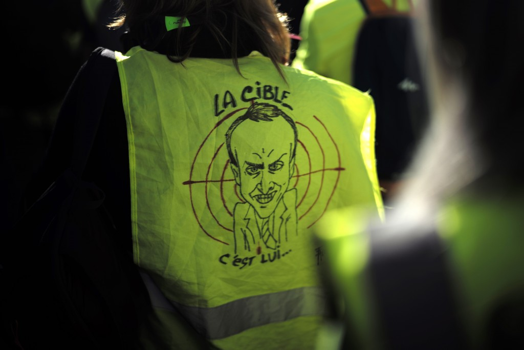 """A protester wears a a yellow vest with a drawing depicting French President Emmanuel Macron and the word """"target"""" during a de demonstration in the str"""
