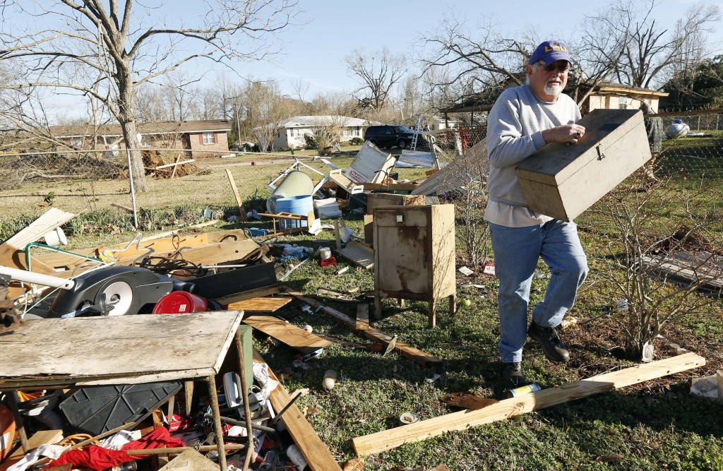 Al Bordelon salvages a tool box from what remains of his mother-in-law's shed in Columbus, Miss., Sunday morning, Feb. 24, 2019, after Saturday's torn