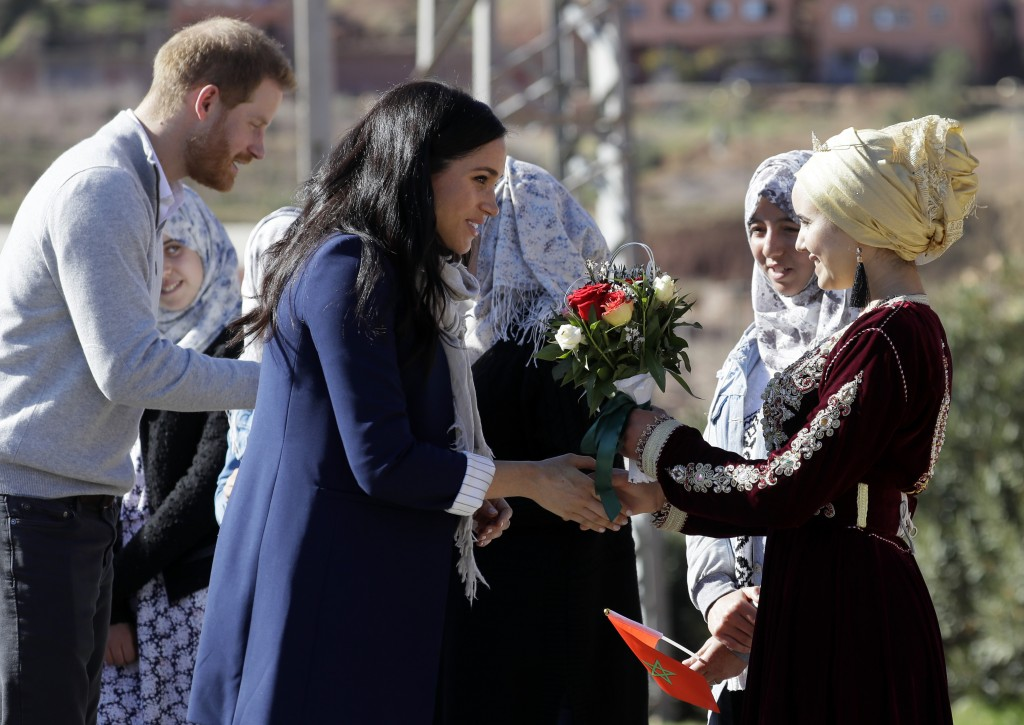 Britain's Prince Harry and Meghan, Duchess of Sussex are greeted as they arrive for a visit to an 'Education for All' boarding house in Asni Town in M