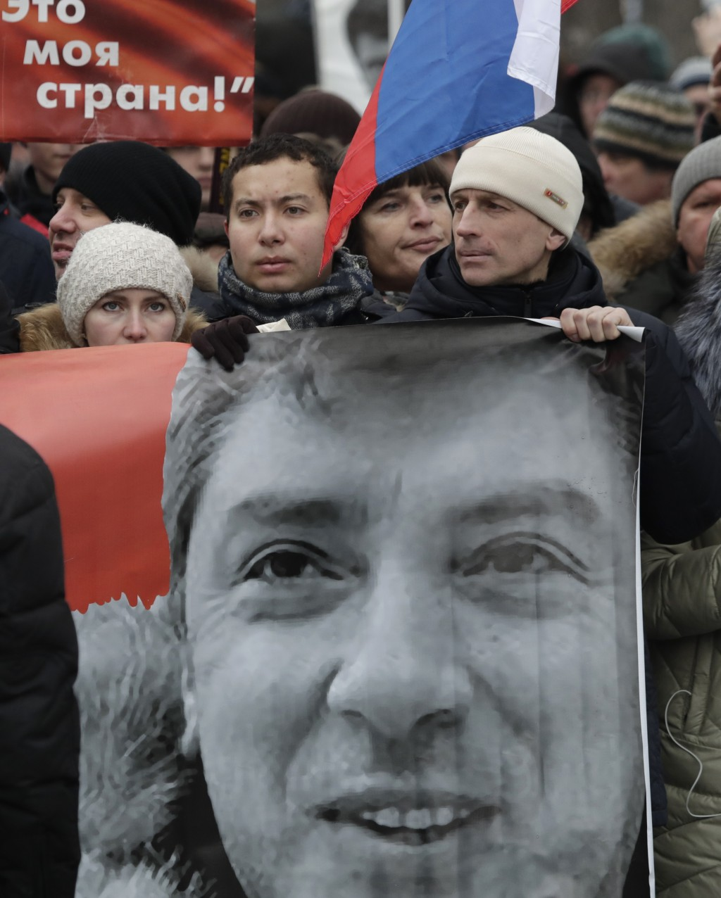 Demonstrators carry a banner with a portrait of Boris Nemtsov march in memory of opposition leader Boris Nemtsov in Moscow, Russia, Sunday, Feb. 24, 2...