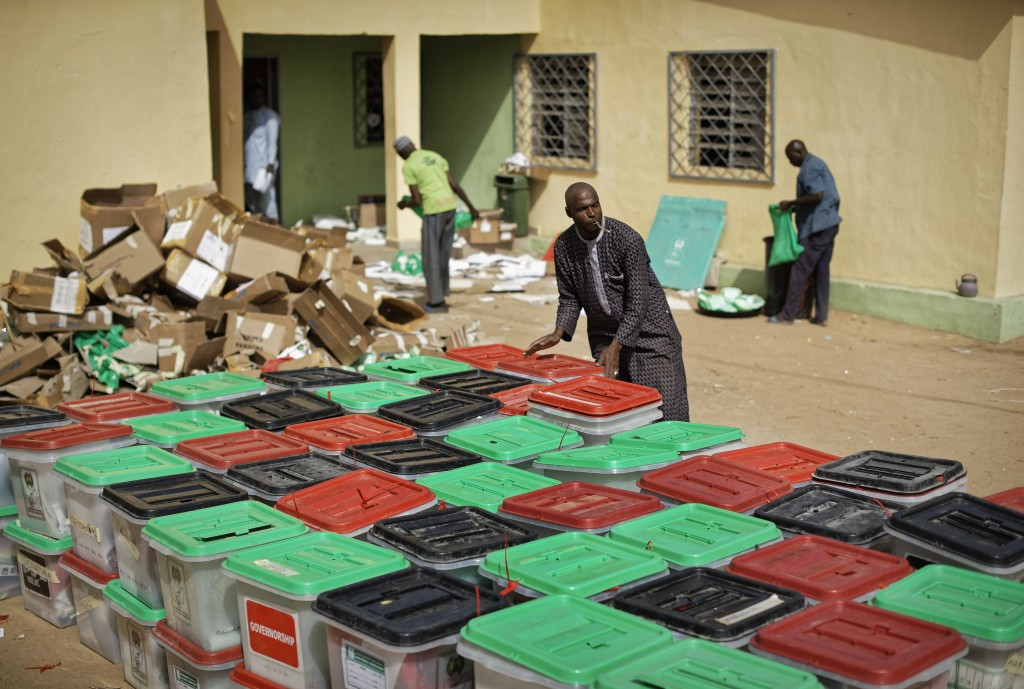 An electoral worker carries and stacks ballot boxes at an electoral commission office in Kano, in northern Nigeria Sunday, Feb. 24, 2019. Vote countin...