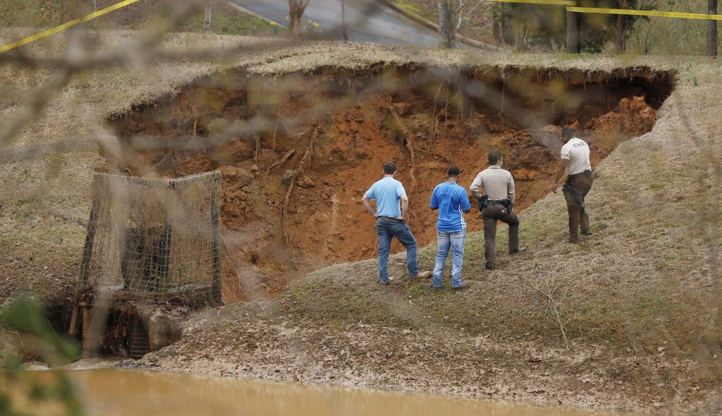 Lafayette County authorities oversee a break in the Audubon Dam in the North Point subdivision in Oxford, Miss., Saturday, Feb. 23, 2019. Homes, highw
