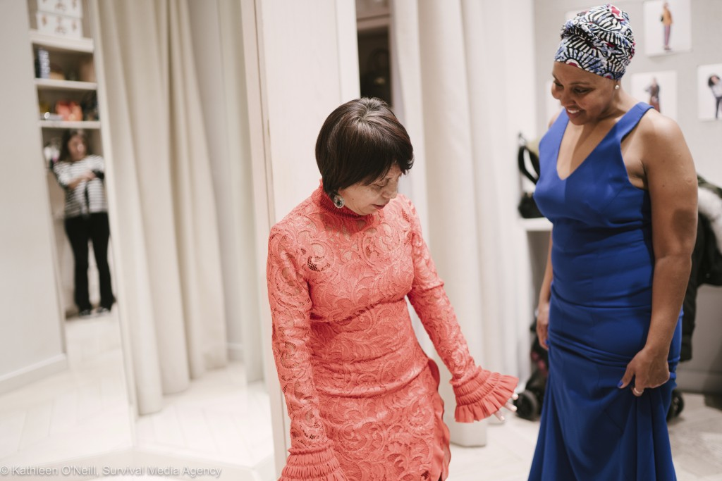 In this photo provided by Survival Media, two women who work in the domestic industry try on dresses for Oscars viewing party at Rent The Runway on We