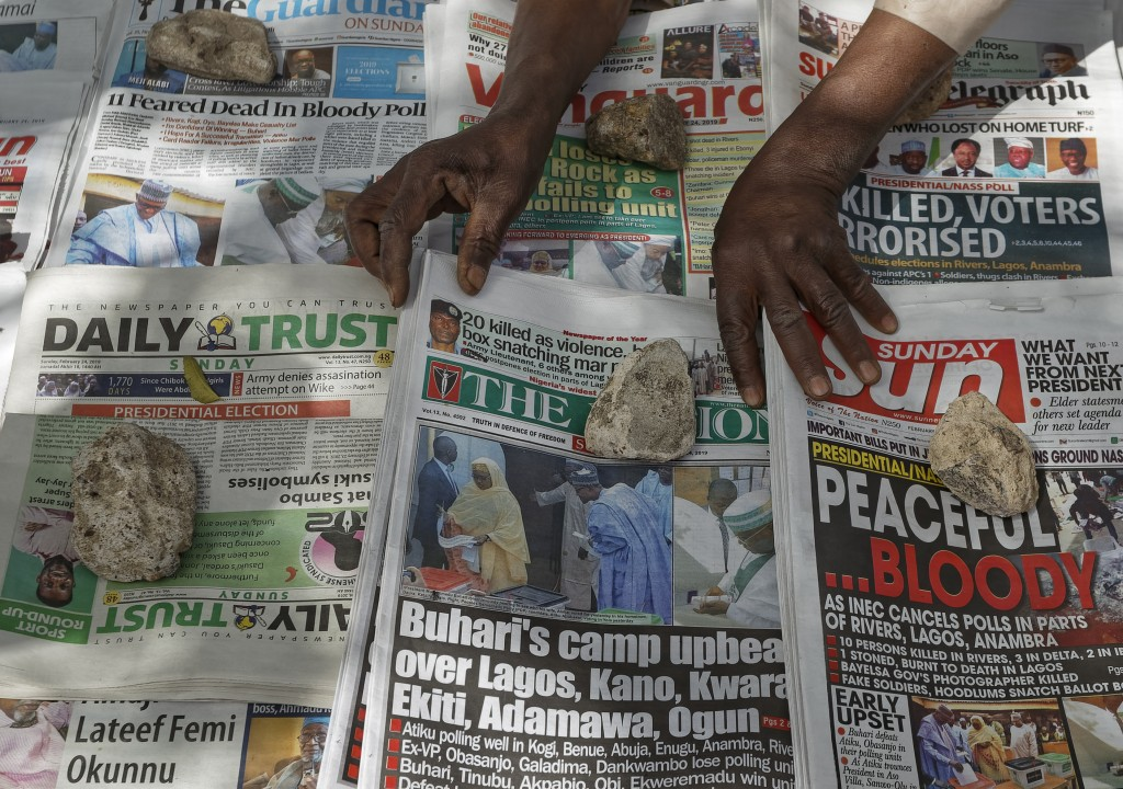 A newspaper vendor uses rocks to stop the day's front pages from blowing in the wind, at a newspaper stand in Kano, in northern Nigeria Sunday, Feb. 2...