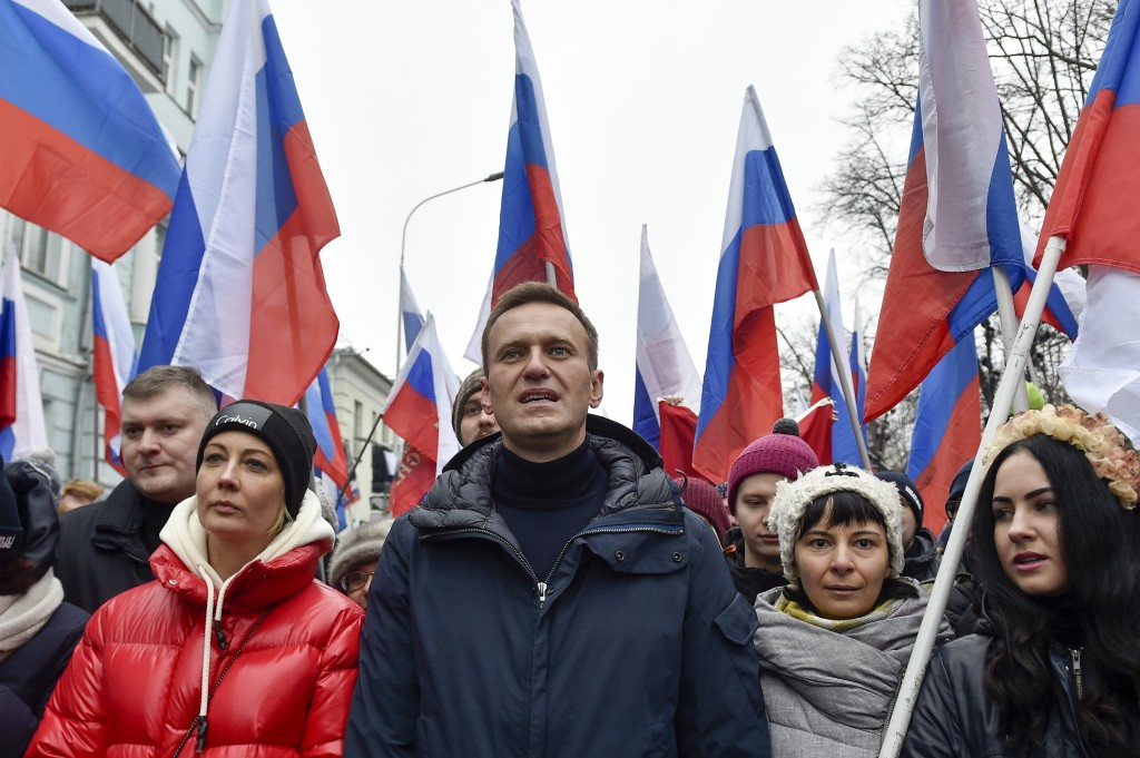 Russian opposition activist Alexei Navalny, center, and his wife Yulia, left, take part in a march in memory of opposition leader Boris Nemtsov in Mos...