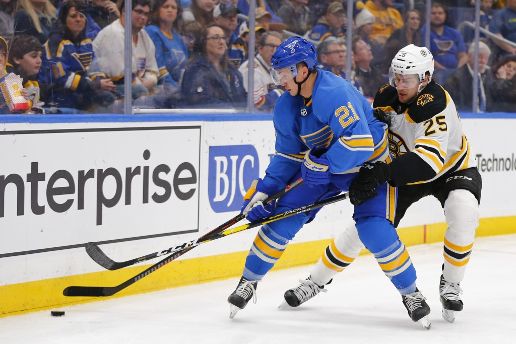 St. Louis Blues' Tyler Bozak, left, fights off Boston Bruins' Brandon Carlo for control of the puck during the second period of an NHL hockey game Sat