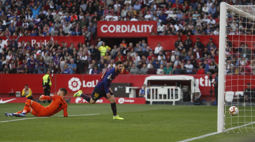 Barcelona forward Lionel Messi scores his side's third goal during La Liga soccer match between Sevilla and Barcelona at the Ramon Sanchez Pizjuan sta...
