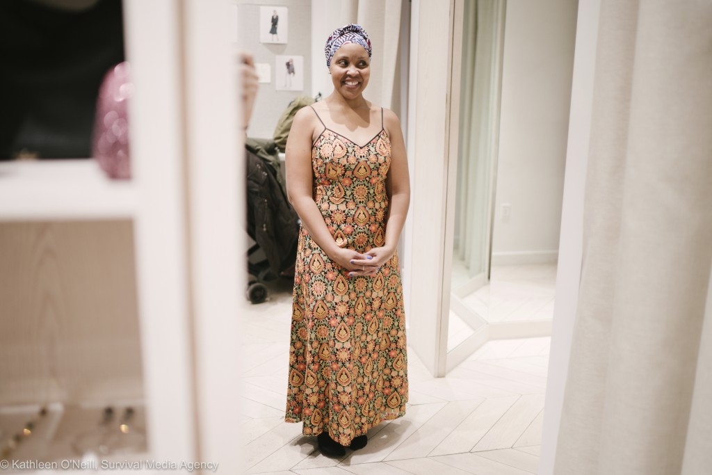 In this photo provided by Survival Media, a woman who works in the domestic industry tries on a dress for a Oscars viewing party at Rent The Runway on...