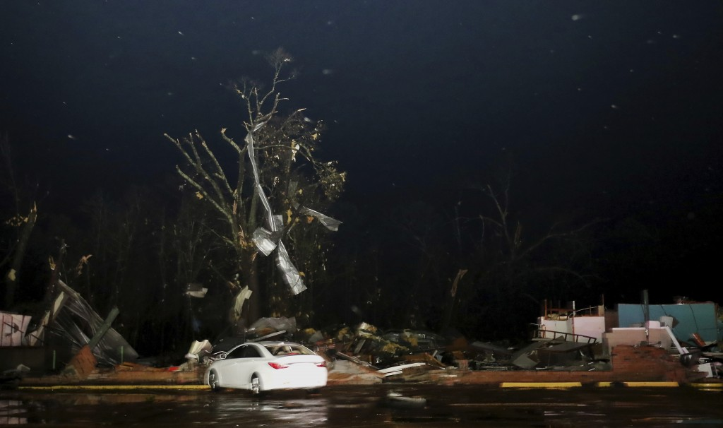 Tin from nearby buildings sits in a tree above a destroyed vacant commercial structure along highway 50 in Columbus, Miss., after a tornado struck the
