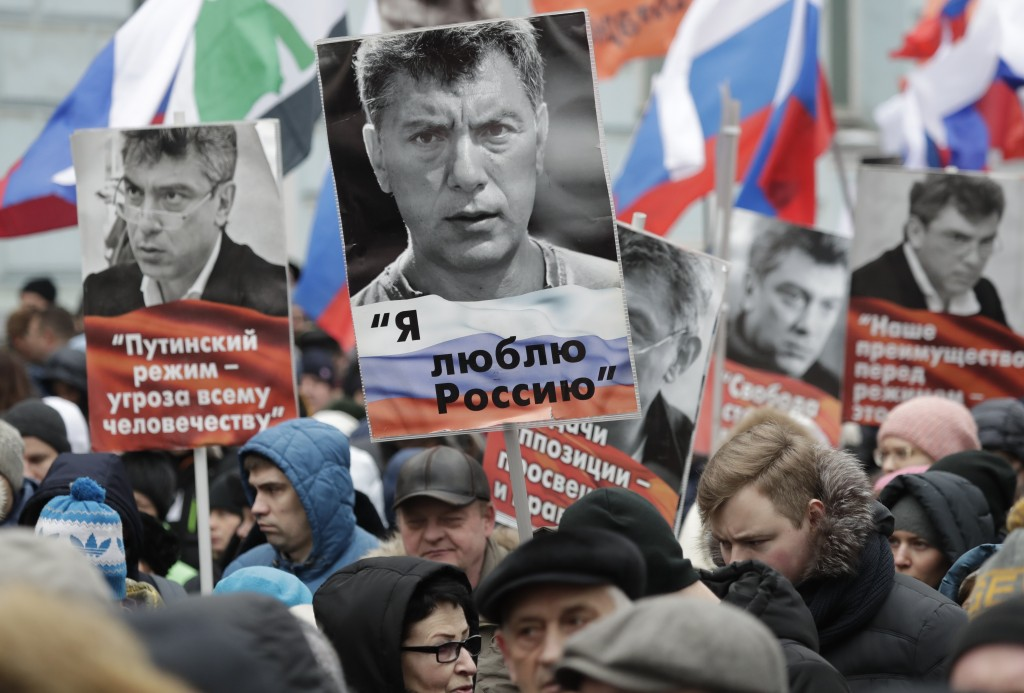 Demonstrators, with flags of different opposition movements and portraits of Boris Nemtsov, march in memory of opposition leader Boris Nemtsov in Mosc...