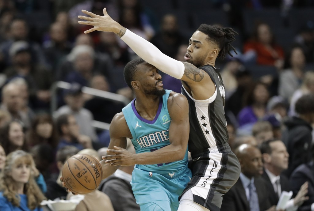 Charlotte Hornets' Kemba Walker, left, is fouled by Brooklyn Nets' D'Angelo Russell, right, during the first half of an NBA basketball game in Charlot