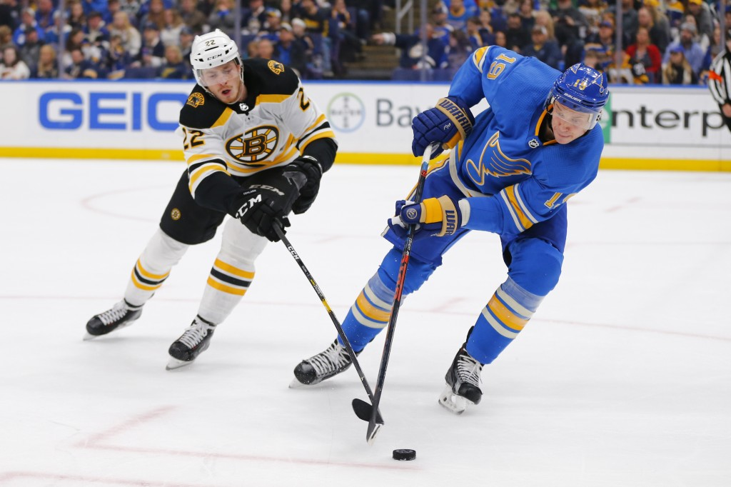 St. Louis Blues' Jay Bouwmeester (19) looks to clear the puck against Boston Bruins' Peter Cehlarik (22), of Slovakia, during the first period of an N