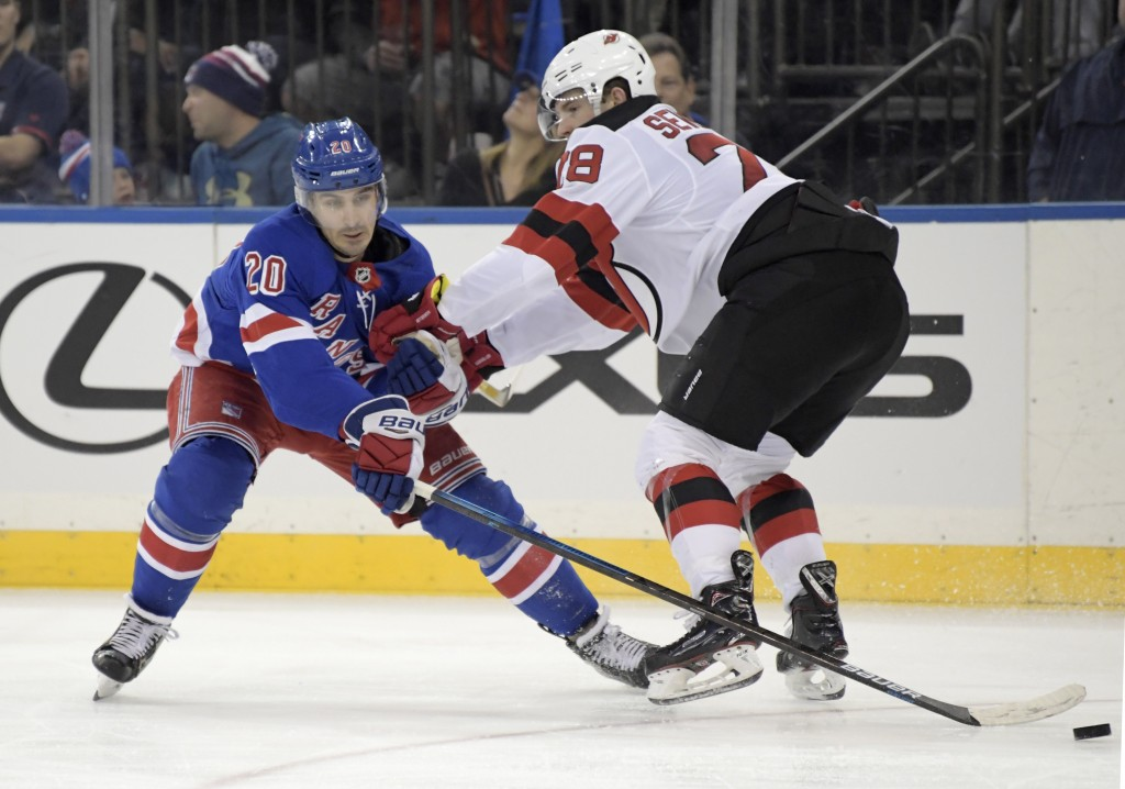 New York Rangers left wing Chris Kreider (20) reaches for the puck as he is checked by New Jersey Devils defenseman Damon Severson (28) during the sec