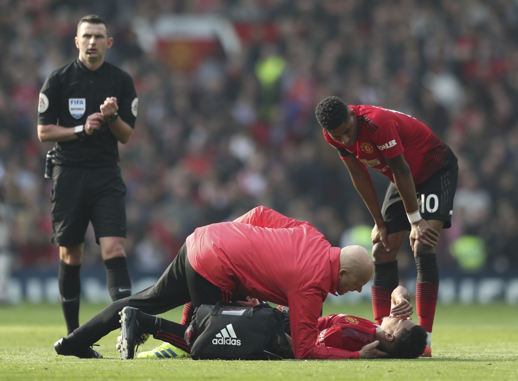 Manchester United's Jesse Lingard lays on the pitch after getting injured during the English Premier League soccer match between Manchester United and