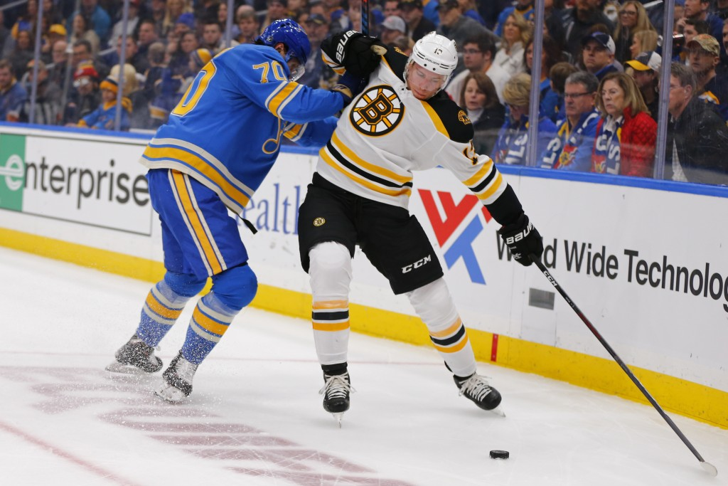 Boston Bruins' Charlie Coyle (13) alludes a check from St. Louis Blues' Oskar Sundqvist (70), of Sweden, during the first period of an NHL hockey game...