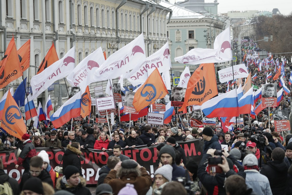 Demonstrators, with flags of different opposition movements, march in memory of opposition leader Boris Nemtsov in Moscow, Russia, Sunday, Feb. 24, 20...