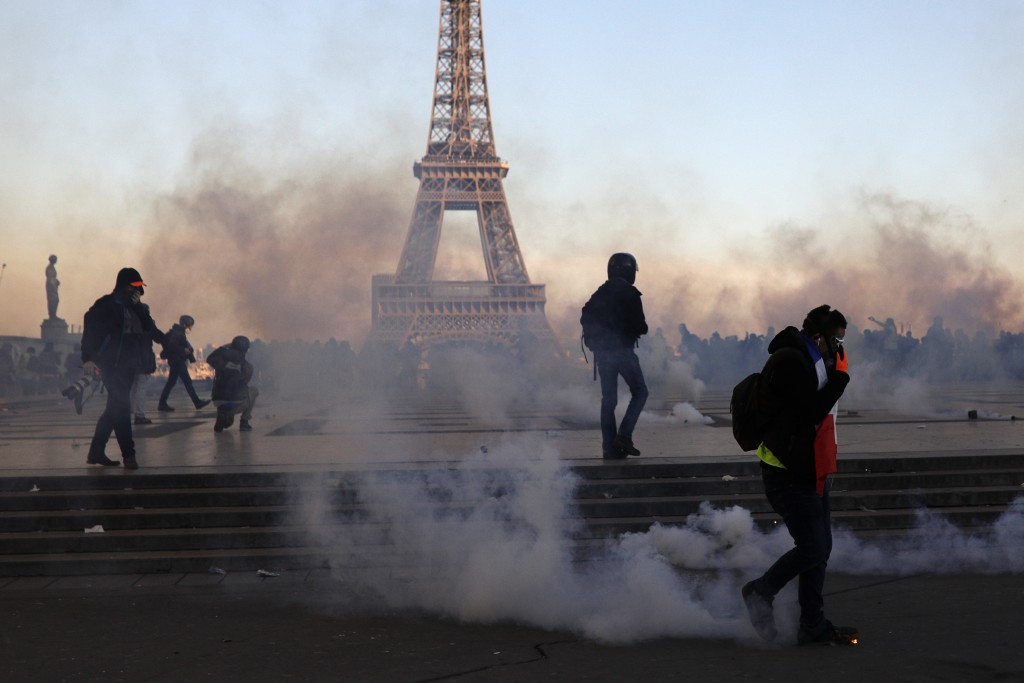 Demonstrators walk through a cloud of teargas on the Trocadero plaza during scuffles with police, in Paris, France, Saturday, Feb. 23, 2019. French ye...