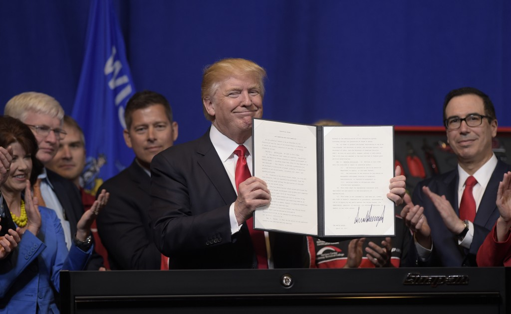 "FILE - In this April 18, 2017 file photo, President Donald Trump holds up the ""Buy American, Hire American"" executive order which he signed during a v"