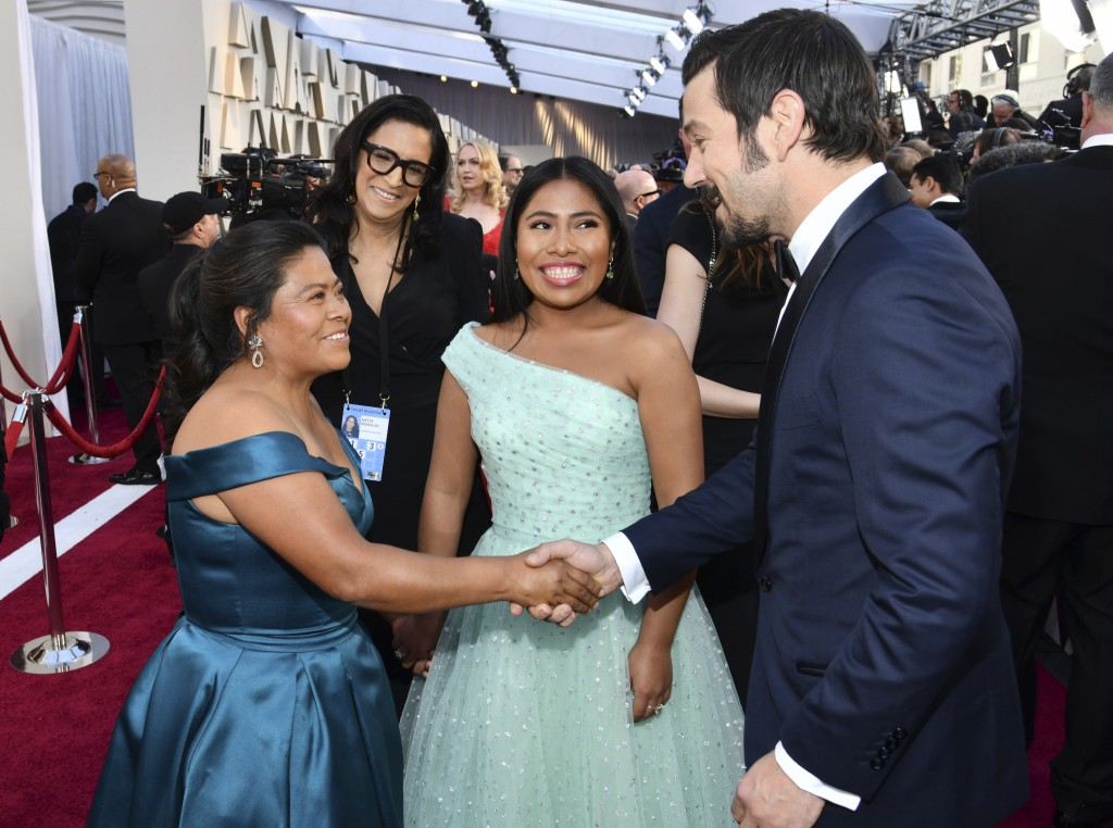 Margarita Martinez Merino, left, shakes hands with Diego Luna, right, as Yalitza Aparicio looks on during arrivals at the Oscars on Sunday, Feb. 24, 2...