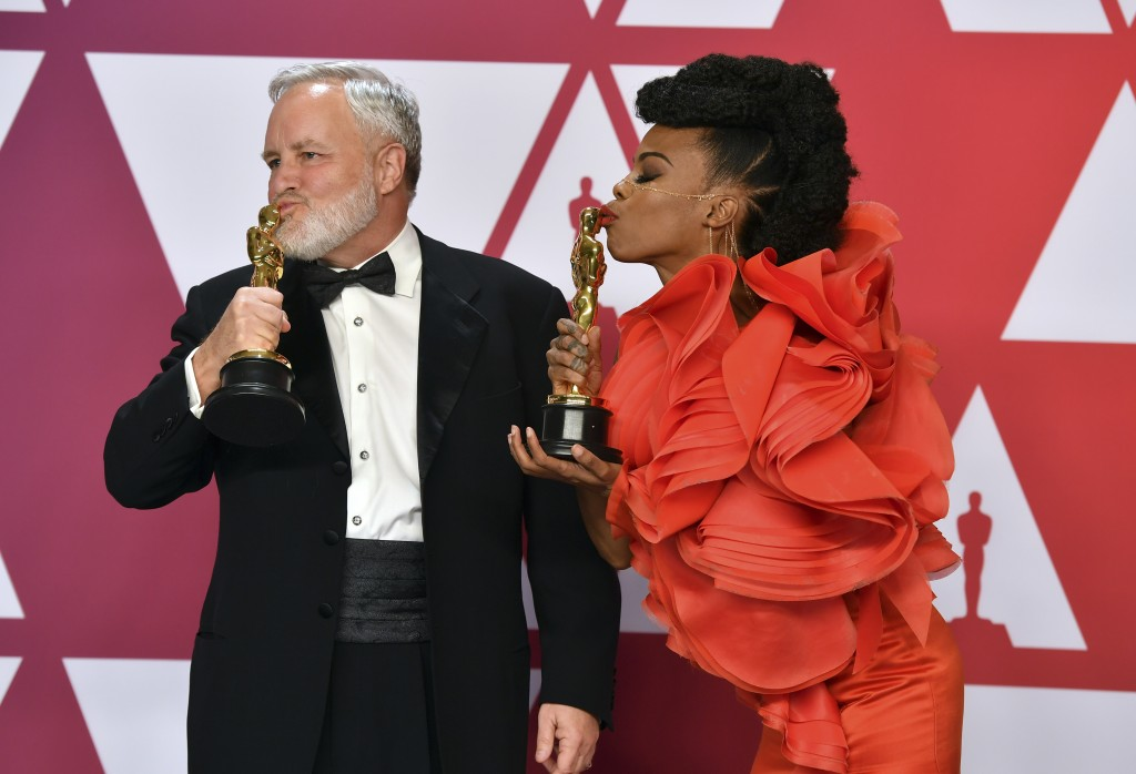 """Jay Hart, left, and Hannah Beachler kiss their awards for best production design for """"Black Panther"""" in the press room at the Oscars on Sunday, Feb. 2"""