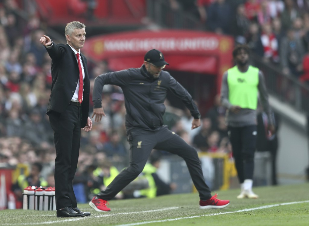 Manchester United manager Ole Gunnar Solskjaer, left, and Liverpool manager Juergen Klopp during the English Premier League soccer match between Manch...
