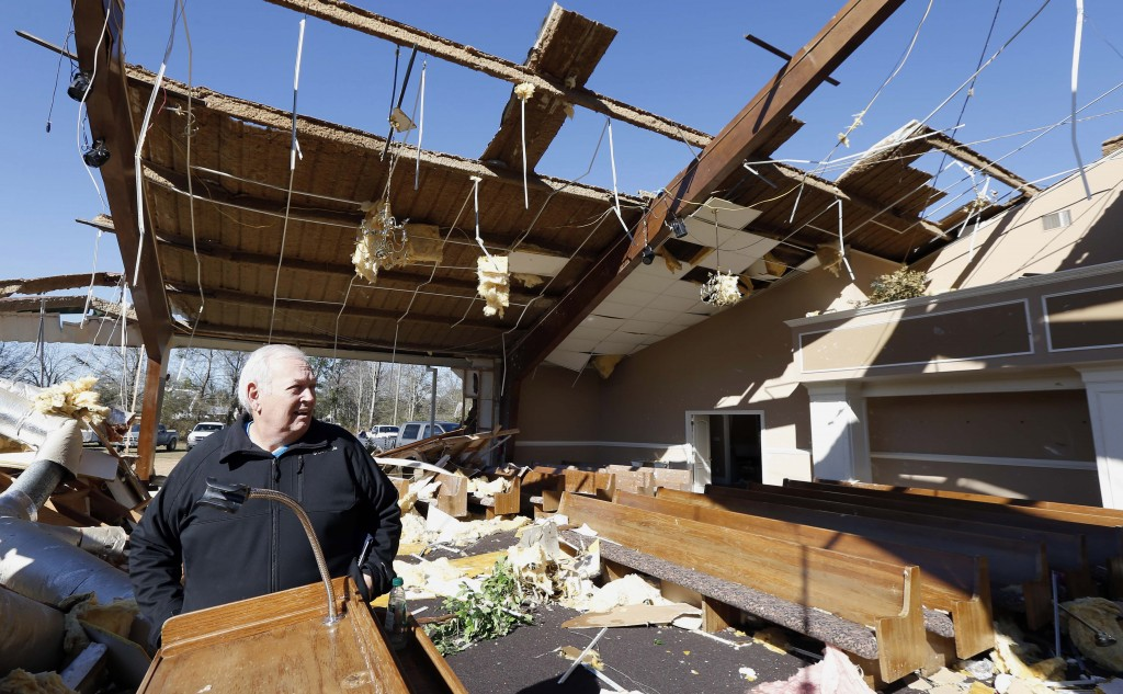 Pastor Steve Blaylock looks over the broken lumber, loose paneling, insulation, and destroyed pews in the First Pentecostal Church in Columbus, Miss.,
