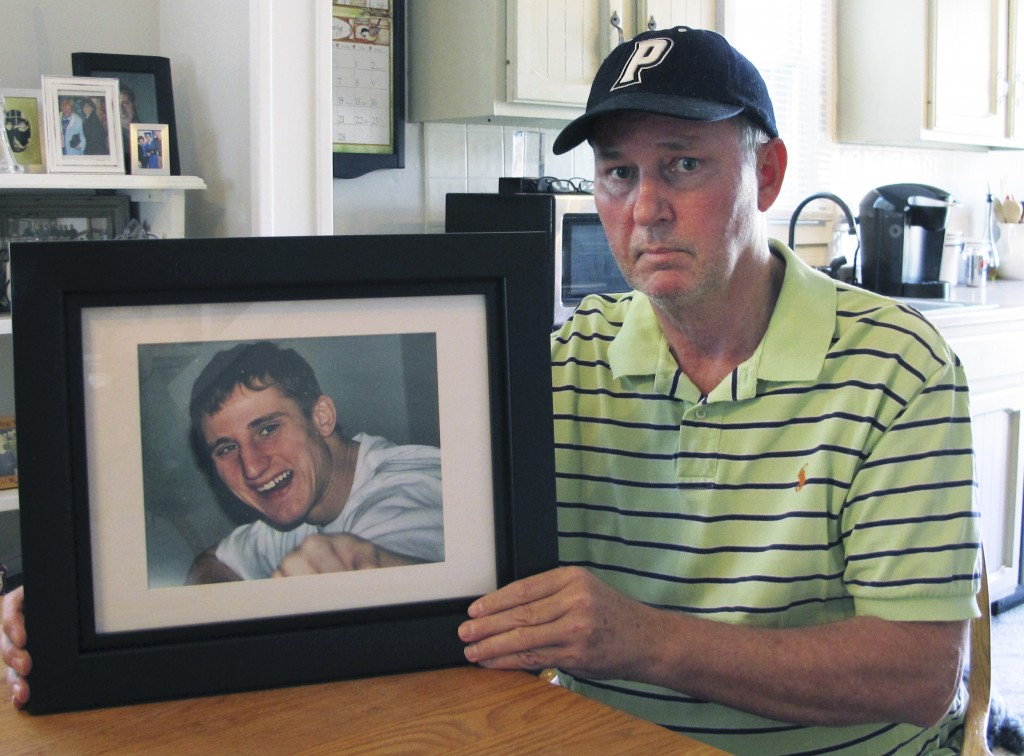 In this Feb. 14, 2019 photo, Dean Palozej poses with a photo of his son, Spencer, in Stafford, Conn. Spencer Palozej died of a fentanyl overdose in la...