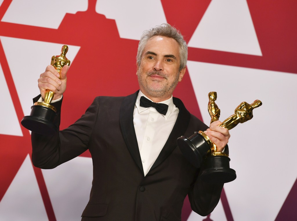 """Alfonso Cuaron poses with the awards for best director for """"Roma"""", best foreign language film for """"Roma"""", and best cinematography for """"Roma"""" in the pr"""