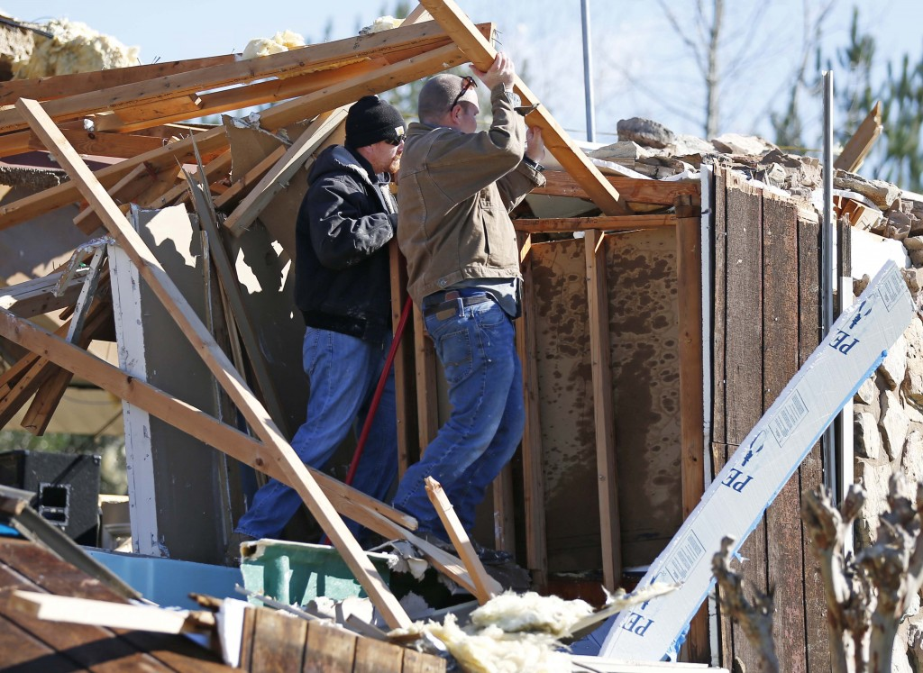 Church members lift beams as they try to determine the status of a Hammond organ that was trapped by tornado debris in the First Pentecostal Church in