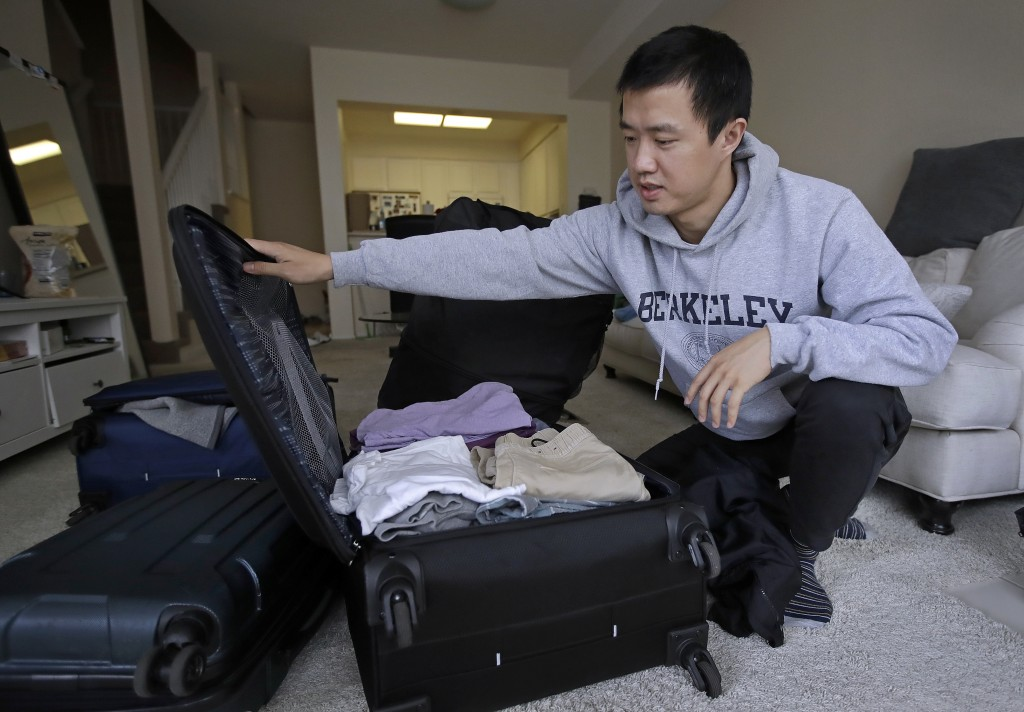 In this Monday, Feb. 4, 2019, photo, Leo Wang packs a suitcase at his home in San Jose, Calif. Wang has found himself trapped in an obstacle course re