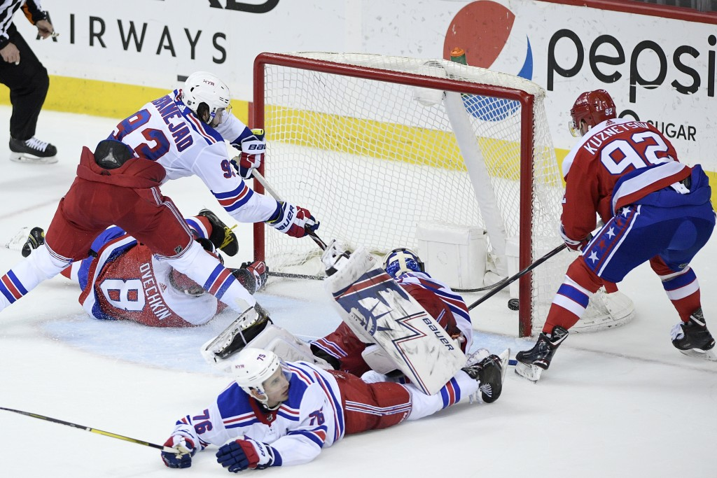 Washington Capitals center Evgeny Kuznetsov (92), of Russia, scores the game-winning goal during overtime of an NHL hockey game against New York Range