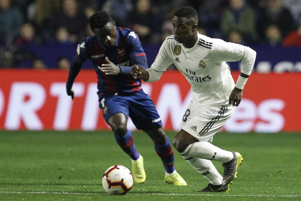 Real forward Vinicius Junior, right, runs with the ball past Levante's Simon during a Spanish La Liga soccer match at the Ciutat de Valencia stadium i...