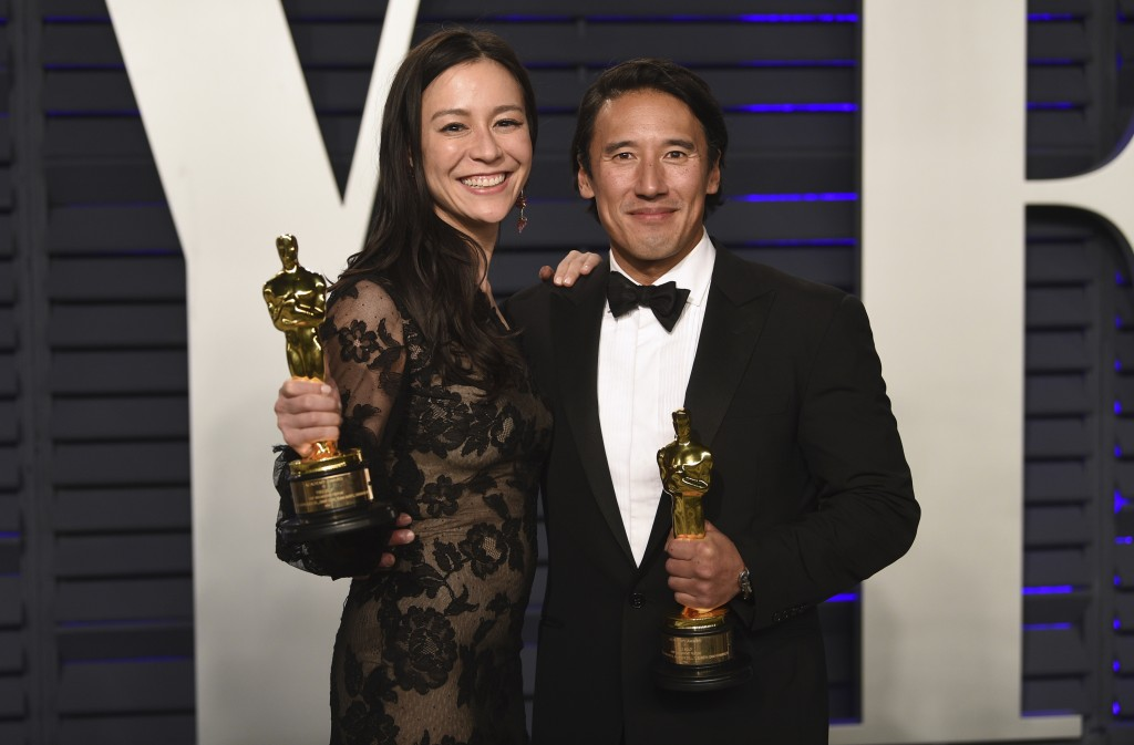 """Elizabeth Chai Vasarhelyi, left, and Jimmy Chin, winners of the award for best documentary feature for """"Free Solo"""", arrives at the Vanity Fair Oscar P"""