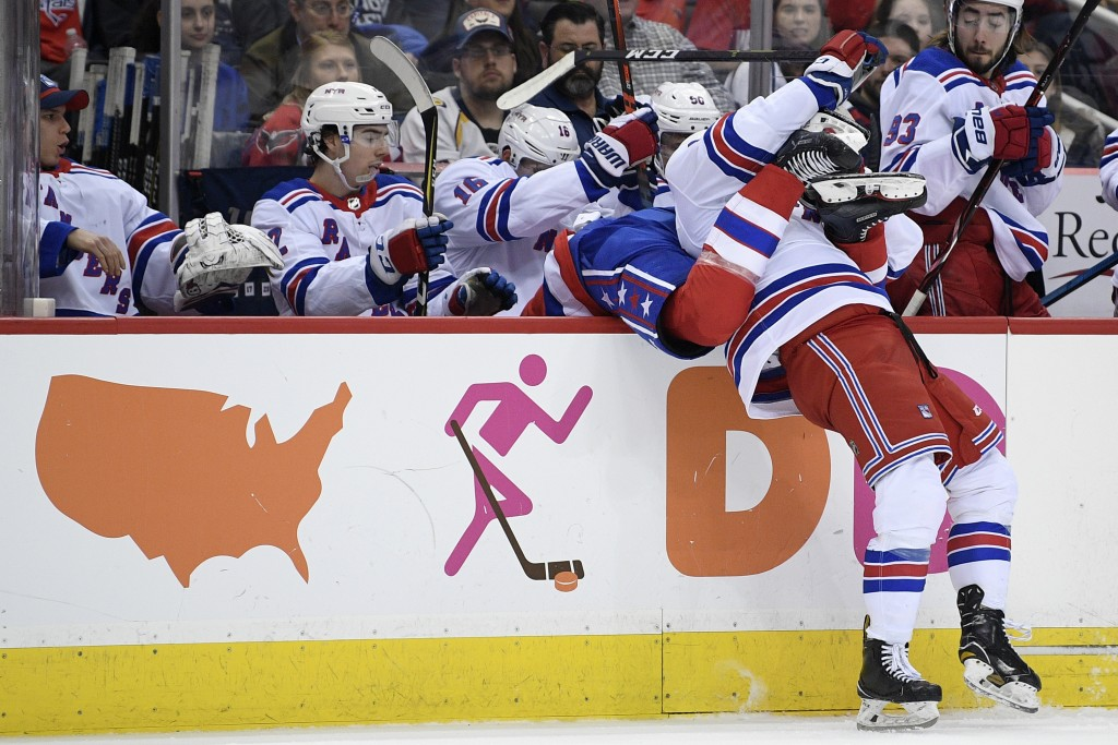Washington Capitals right wing Brett Connolly (10), center, falls into the New York Rangers bench with the help of Rangers left wing Connor Brickley,