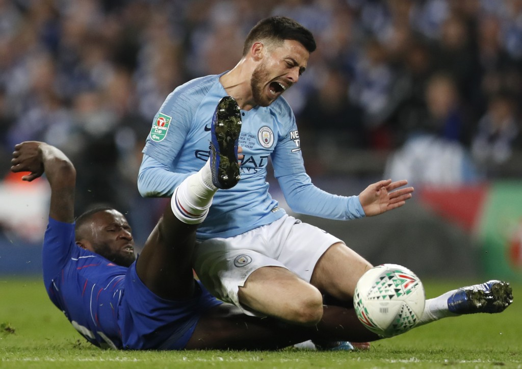 Chelsea's Antonio Rudiger, left, tackles Manchester City's David Silva, right, during the English League Cup final soccer match between Chelsea and Ma