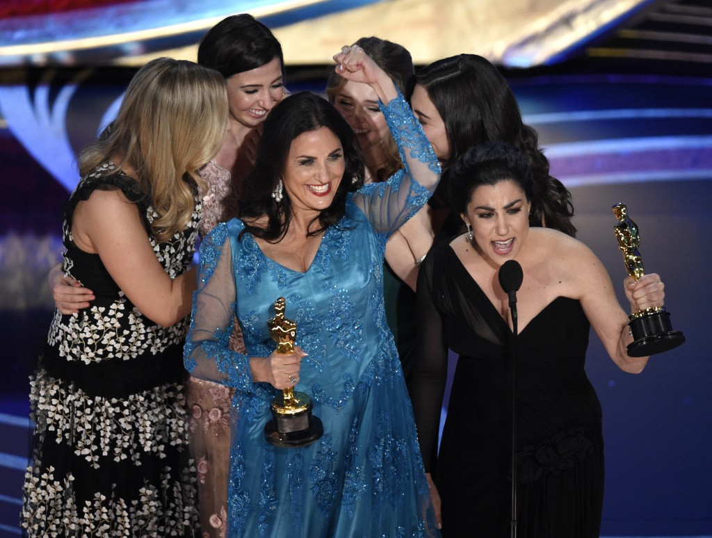 """Melissa Berton, center left, and Rayka Zehtabchi accept the award for best documentary short subject for """"Period. End of Sentence."""" at the Oscars on S"""