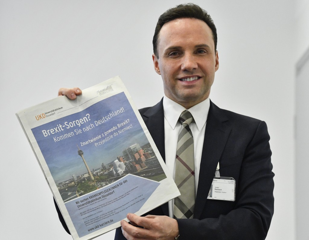 """In this Tuesday, Feb. 12, 2019 photo, the Director of Nursing Torsten Rantzsch poses with his advertisement in Polish newspapers in the UK, reading """"B"""