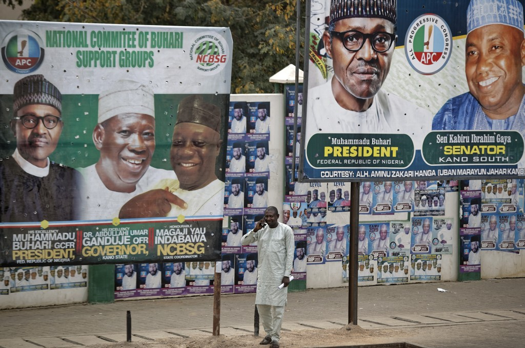 A man takes a call on his cellphone as he stands between two billboards showing Nigeria's President Muhammadu Buhari and other party officials, in Kan...